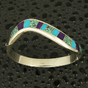 Elegant curved channel bracelet in sterling silver inlaid with spiderweb turquoise, sugilite and turquoise.