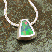 Genuine Australian opal inlaid in a handmade sterling silver pendant. The pendant is inlaid with one piece of unique rolling flash multi-color Australian opal.