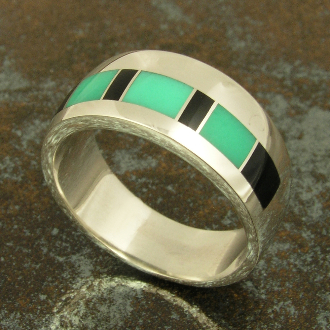 "Handmade sterling silver band inlaid with green chrysoprase and black onyx. The 3 pieces of translucent chrysoprase appear to ""glow"" when you hold the ring in the sunlight."