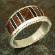 Handmade sterling silver band inlaid with red dinosaur bone and black onyx by jewelry artist Mark Hileman. Four pieces of inlaid black onyx accent the five pieces of red dinosaur bone with black webbing.