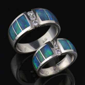 Matching handmade his and hers sterling silver wedding ring set inlaid with Australian opal accented by white sapphires. Beautiful inlaid Australian opal surrounds three round brilliant cut white sapphires in each of these unique wedding bands.