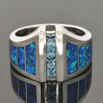 Lab created opal ring with blue topaz accents set in sterling silver. This man's ring is inlaid with bright blue-green synthetic opal that is is a great match with sparkling blue topaz.