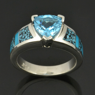 Sterling silver blue topaz ring inlaid with alternating spiderweb turquoise and turquoise. Sky blue 2.25 carat trillion cut topaz accented by blue spiderweb turquoise with black matrix.
