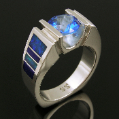 Woman's blue topaz sterling silver ring inlaid with lapis and Australian opal. The sparkling round blue topaz weighs 1.4 carats and looks great with the lapis and blue Australian opal.