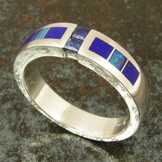Man's sterling silver band featuring 2 channel set blue sapphires accented by inlaid Australian opal and lapis. The two princess cut blue sapphires have a total weight of .30 carats and are high quality.