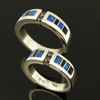 Unique his and hers sterling silver black diamond wedding set inlaid with Australian opal and black onyx. Matching handmade bands feature 2 channel set round black diamonds flanked by alternating onyx and blue-green Australian opal inlay.