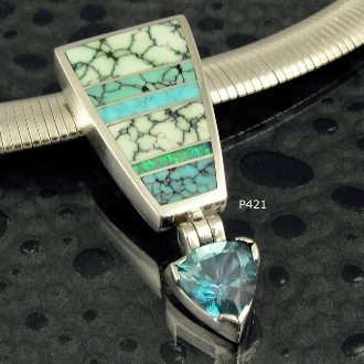 Sterling silver pendant inlaid with spiderweb turquoise, variquoise, Australian opal, and turquoise. Trillion cut blue topaz weighing 2.5cts. dangles from hinged connnection.