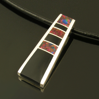 Contemporary handmade sterling silver pendant inlaid withlab opal and black onyx. 3 pieces of lab created opal mixed with 3 pieces of black onyx are inlaid in this contemporary design.