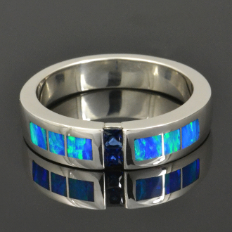 Man's sterling silver wedding band featuring 2 channel set blue sapphires accented by lab created opal. The lab created opal in this ring is a nice blue-green color.